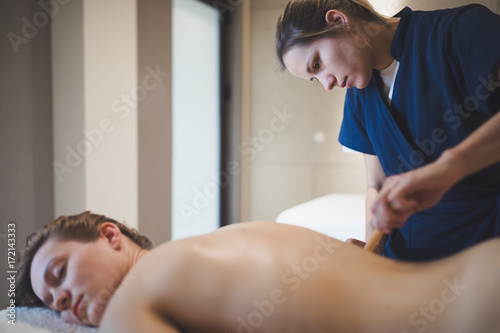 Massage therapist using wooden tool to massage patient