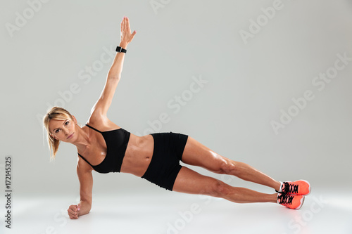 Sticker Young healthy sportswoman doing planking