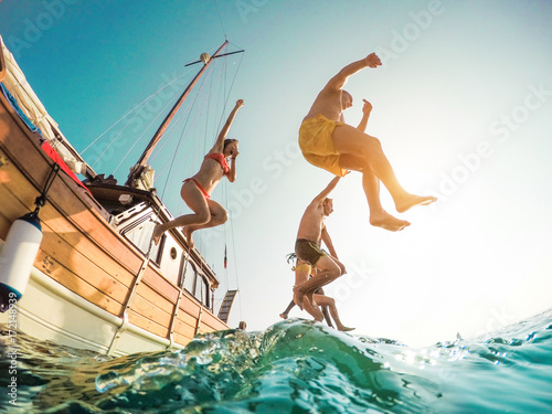 Happy friends diving from sailing boat into the sea - Young people jumping inside ocean in summer excursion day - Vacation, youth and fun concept - Main focus on left man - Fisheye lens distortion