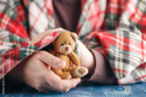 symbol of care, male hand hold bear toy
