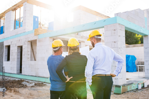 Architects and worker at the construction site. - 172152371
