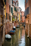 Old narrow street with a boats in Venice, Italy