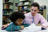 Portrait of teacher assisting little boy with homework in the library - 172170786