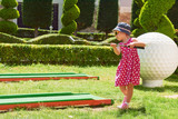Child playing mini - golf on artificial grass. - 172172774