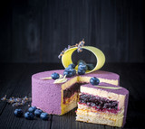 Delicious lavender cake with blueberries on black wooden table - 172175719