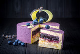 Fototapety Delicious lavender cake with blueberries on black wooden table