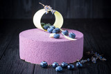 Delicious lavender cake with blueberries on black wooden table - 172175963
