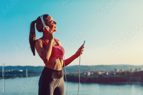 Wall mural Young woman in sports clothes listen to music via headphones and smartphone
