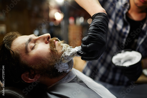 Shaving ritual in barbershop - barber applying foam before procedure Plakat