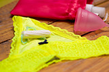 Close up of a a menstruation cotton tampon over a yellow woman underwear, and a menstrual cup and a blurred red cotton bag, in a wooden table, in a blurred background - 172199191