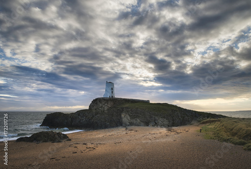 Staande foto Cappuccino Stunning Twr Mawr lighthouse landscape from beach with dramatic sky and cloud formations