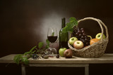 Still Life image of Fresh grapes and wine bottle in the brown basket with glass of wine and and fruits all put on wooden plank and green leaf - 172203102