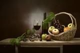 Still Life obraz świeżego winogron i butelkę wina w brązowym koszu ze szklanką wina i owoców wszystkie na drewnianej desce i zielonym liści