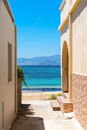 Foto op Canvas Smal steegje Typical Greek narrow street with view over blue sea. Naxos island. Cyclades. Greece.
