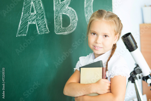 Young girl writing ABC on green chalkboard Poster