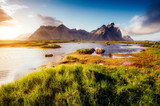 Fototapety Beautiful view of the green hills glowing by sunlight. Location famous place Stokksnes cape, Vestrahorn (Batman Mountain), Iceland, Europe