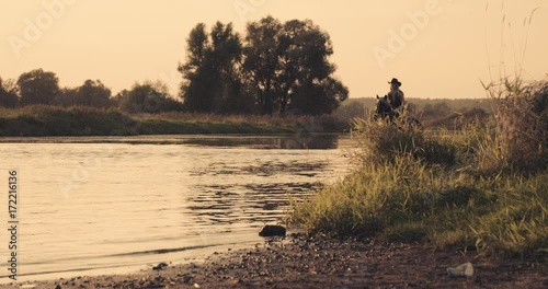 Wall mural Slow motion 240fps shot of cowboy girl riding horse in water of sunset river