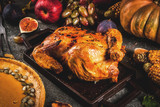 Thanksgiving Day food. Roasted whole chicken or turkey with autumn vegetables and fruits: corn, pumpkin, pumpkin pie, figs, apples, on dark grey background, copy space - 172223777