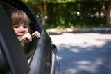 Teenage girl looking through car window - 172246549