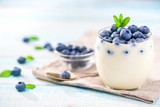Clear jar of yogurt with blueberries over on wooden background