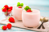 strawberry yogurt and metal spoons on a wooden background