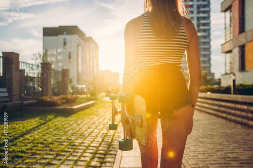Skateboarder girl sunrise lifestyle. Longboard