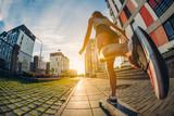 Speeding skateboarding young girl at city. Sunrise. Lifestyle. Longboard