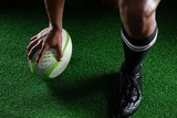 High angle view sportsman kicking rugby ball