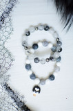 Fashion stone bracelets. Lace and fur background. Wooden white texture