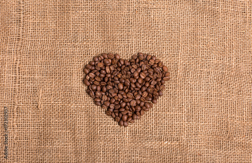 Fotobehang Koffiebonen Coffee grain heart on fabric textured brown background