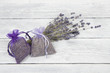 Two lavender sachets and a bunch of dried lavender flowers on a white wooden planks background