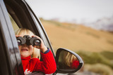 little girl looking through binoculars travel by car in mountains - 172328742