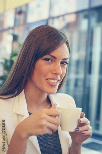Smiling woman holding cup of coffee and looking at camera. Poster