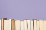 Row of books on a lavender purple background with space for copy - 172332943