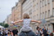 A girl with arms spread sits on her father's shoulders at a city party