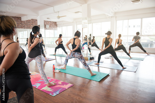 Fototapeta Group women stretching and practices yoga in a class, healthy lifestyle and fitness concept