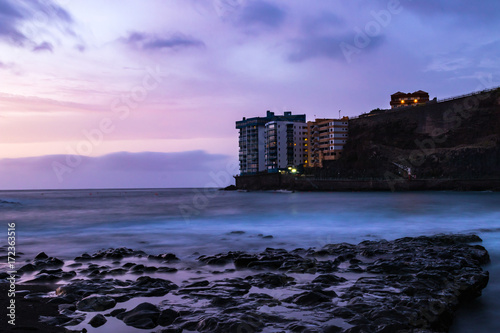 Fotobehang Purper Sunset of long exposure in Mesa del Mar beach with rock more detailed, Tacoronte, Tenerife, Canary Islands, Spain.
