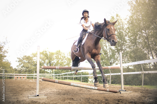Girl riding a horse and jumping and obstacle