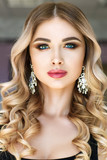 Beautiful woman portrait with curly hair, glamour make up and shiny earrings.