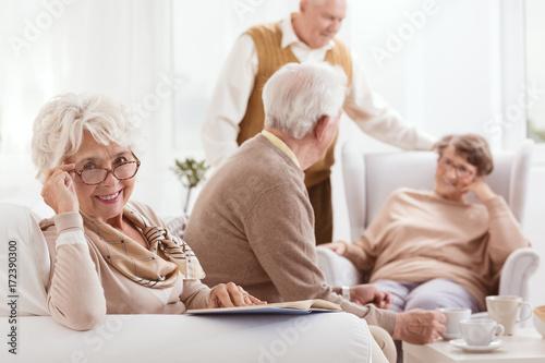 Uśmiechnięta babcia czyta książkę