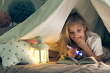 Girl with flashlight reading book - 172391946