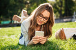 Pleased brunette woman in eyeglasses lying on grass