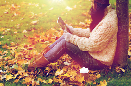woman with tablet pc and coffee in autumn park - 172417325