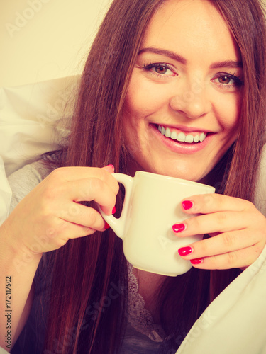 Poster Smiling woman holding cup of drink in bed