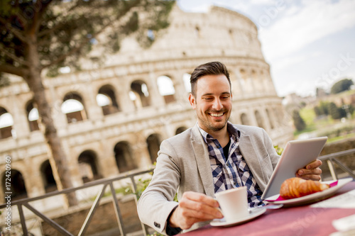 Young man sitting and having a cup of coffee in Rome, Italy Poster