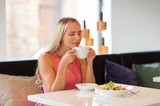 woman eating and drinking coffee at restaurant - 172422911