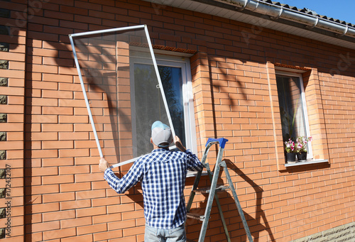 Worker install mosquito net or mosquito wire screen on brick house window. - 172432107