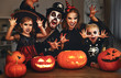 Leinwanddruck Bild - happy family mother father and children in costumes and makeup on  Halloween.