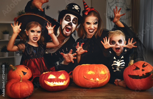 Leinwanddruck Bild happy family mother father and children in costumes and makeup on  Halloween.