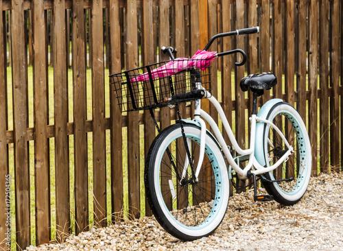 Foto op Plexiglas Fiets Beach bike parked against a fence with umbrellas in its basket